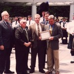 National Vice President John Kinane, presenting John Walsh with an Honorary Life Membership to the Emerald Society of the Federal Law Enforcement Agencies, on the set of America's Most Wanted, during ceremonies at the Law Enforcement Memorial, Washington D.C., with Chairman, Mike Haggerty; President, Tom Smart; Vice President, Danny Crawford; and the Chicago Police Emerald Society Pipe Band.